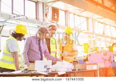 Supervisor with workers examining blueprints at table in industry