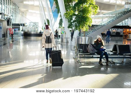 Passengers in the airport waiting room. Modern building. Comfort for the passengers.