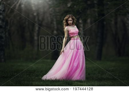 Beautiful sensual blond girl in pink long dress is kidding in the park.