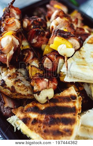 Grilled chicken meat skewers rolled with bacon. barbeque skewers with vegetables and roasted pizza bread