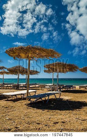 Paros island, Cyclades, Greece. Straw umbrellas and beach loungers on Golden Beach.
