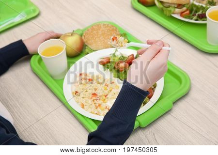 School girl eating delicious food at table