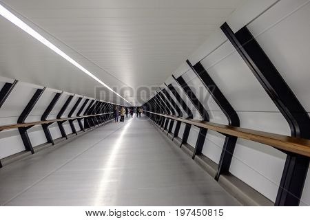CANARY WHARF LONDON UK - 7 JANUARY 2016: Commuters walking through interesting geometric shapes and lines of new Crossrail Place tunnel walkway in Canary Wharf London's Docklands area