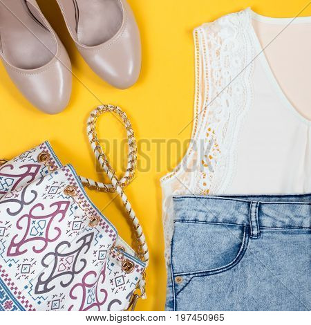 Stylish female summer clothing collection overhead on a bright yellow background