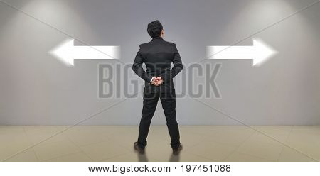 Businessman standing in doubtthinking the two different choices indicated by arrows pointing in opposite direction business decision concept