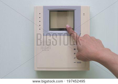 Human finger pushing button of video intercom equipment