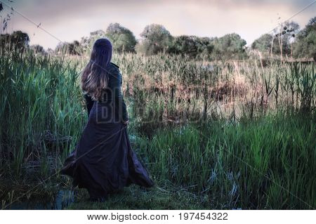 A woman in antique clothes near a swamp