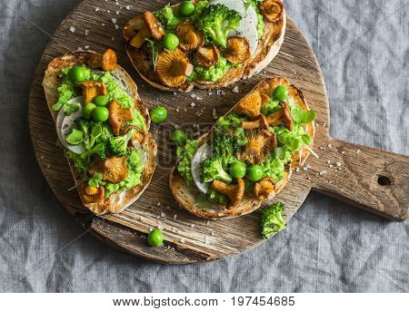 Chanterelles and green peas sandwiches on rustic cutting board on grey background top view. Sandwiches with mushrooms and green peas puree. Vegetarian snack
