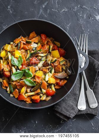 Quick ratatouille in a cast iron skillet on a dark background top view. Steamed vegetables - vegetarian food concept