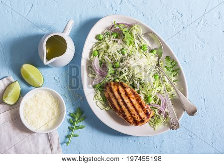 Grilled chicken breast and cabbage green pea and parmesan coleslaw. Healthy balanced food. On a blue background top view