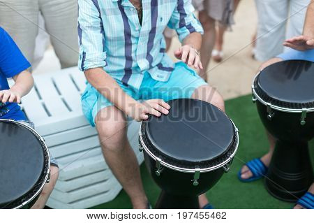 drum, percussion instruments and culture concept - closeup on hands of musicians playing withl turkish darbuka, summer outdoors concert performance, ethnic rhythm performance, selective focus