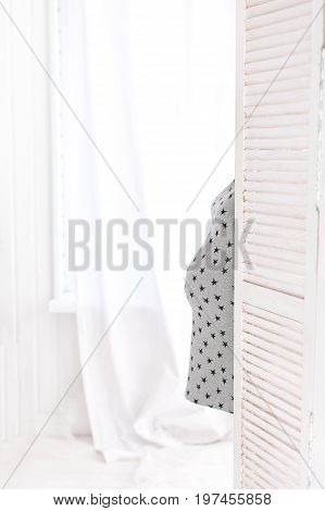 pregnancy, surprise, family concept - hide and seek game of pretty round stomach, standing young girl on white background of window, expectant lady hid behind the door, grey dress with stars pattern