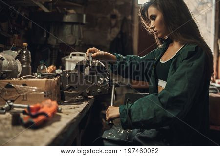 Girl worker in green overalls sits in workshop near vice. In vice she clamps detail.