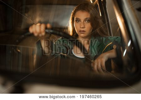 Portrait of woman driver behind steering wheel of car. View through windscreen. Reflections of light are visible on window.