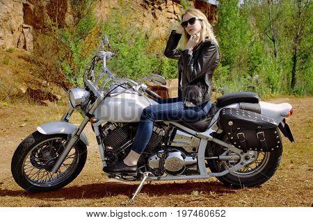 Biker blonde girl in black leather jacket sitting on motorcycle