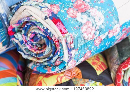 homemade, garment industry, craft concept. macro on a perfectly sewn part of the bedspread for the bed with images of weightless pink carnations twisted into roll