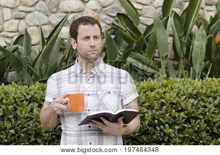 Optimistic man looking out with book and coffee mug in hand.