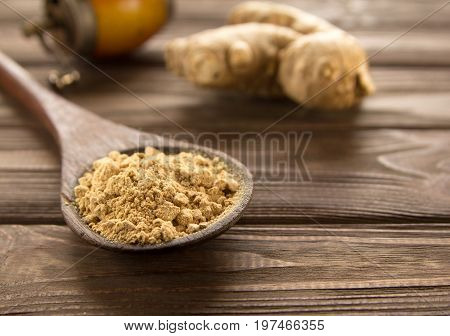 Spice ginger powder in a wooden spoon on dark wooden background vintage hand mill and ginger root. Close-up.
