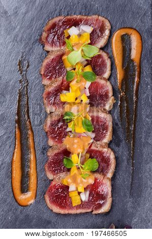Raw and fresh tuna meat with sause and fresh vegetable on stone.