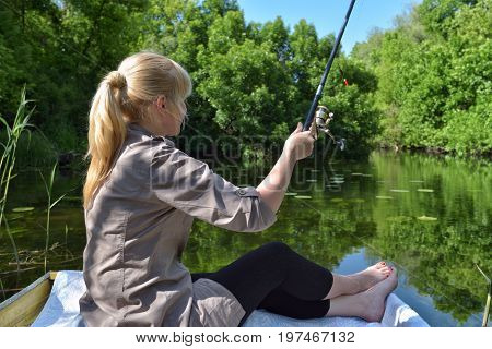 A girl in a boat is fishing in the lake. Picturesque view of wild nature.
