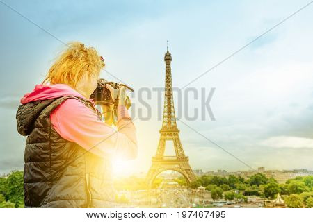Professional photographer with camera on Place du Trocadero takes shot of Tour Eiffel at sunset. Traveler woman in Paris, France, Europe. Eiffel Tower on blurred background. Travel and tourism concept
