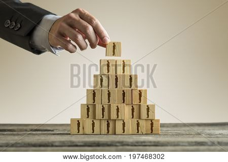 Businessman Building A Pyramid Of Wood Blocks With People Silhouettes