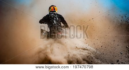 ATV rider creates a large cloud of dust and debris