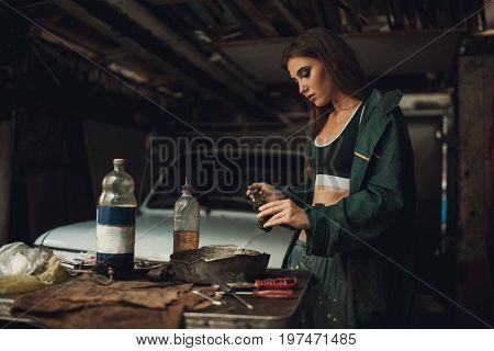 Girl worker in green overalls and t-shirt stands in workshop among tools and lubricates spare parts from car. In her hands she holds brush next to her there is bottle of grease.