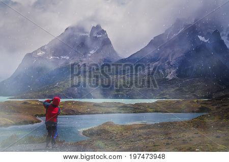 Girl taking pictures of the the impressive Cuernos del Paine peaks during snowfall, Torres del Paine National Park, Chile, South America