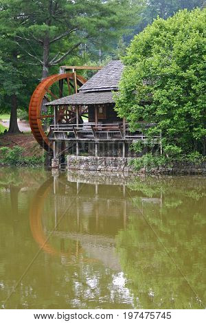 a restored gristmill reflected in a pond