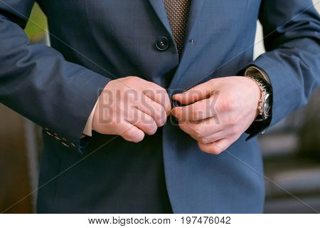 wedding men's hands button up, A man in a blue suit fastens a button, preparation for a wedding