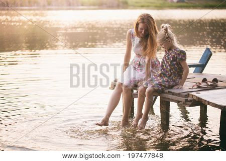 Mother And Daughter Sitting On The Pier