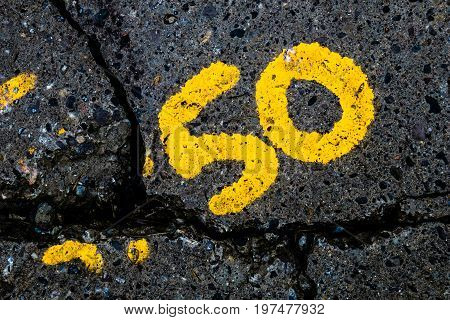 yellow number 50 on a cracked wet concrete surface