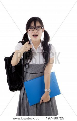 Portrait of female high school student looks angry scolding at the camera while pointing. Isolated on white background