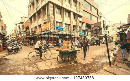 BANGALORE, INDIA - FEB 14, 2017: Chaos on city with cycles and rushing people on street full of stores on February 14, 2017. With population 8.52 million Bangalore is 3-rd most populous indian city