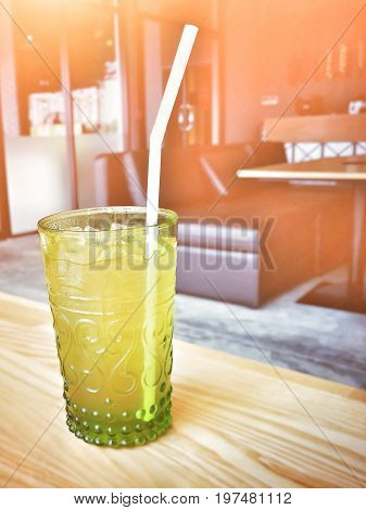 Cold lemongrass juice (yelow vegetable or fruit juice) with straw in a glass; put on wooden surface; blurred sofa and table background (relax time), flare light added, copy space on the right.
