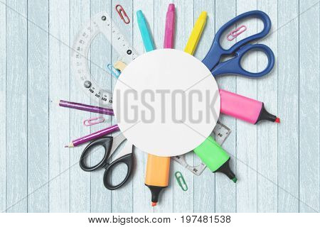 Top view of a blank round paper over school supplies on the table