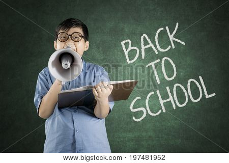 Portrait of boy student yelling on megaphone while holding a book with back to school word on chalkboard in classroom