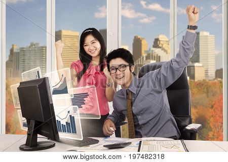 Picture of Asian business people expressing their success while working with virtual growth graphs on the computer screen