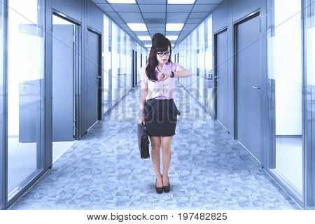 Image of pretty businesswoman looks hurry while looking at her wristwatch and standing in the office corridor