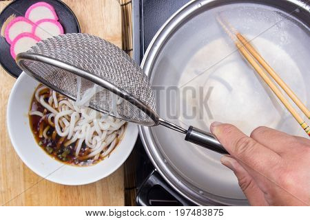 Chef putting udon noodle to cup / Cooking Tempura Udon concept
