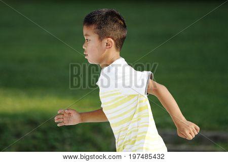 Japanese Boy Running On The Grass (second Grade At Elementary School)
