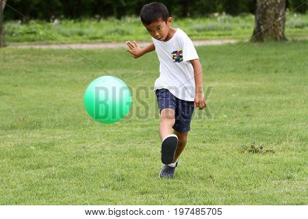 Japanese Boy Playing With Soccer Ball (second Grade At Elementary School)
