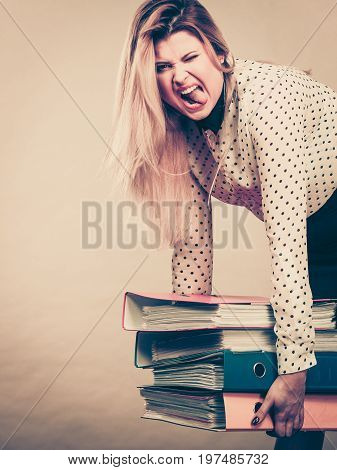 Woman holding many heavy colorful binders with documents. Office bookkeeping objects concept.
