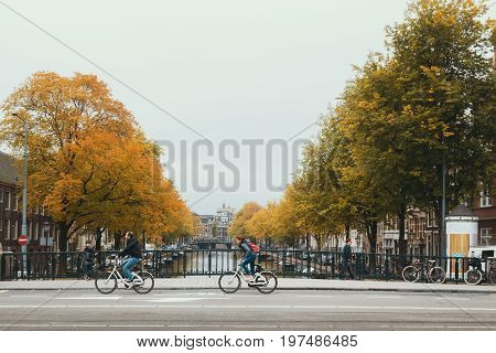 Amsterdam, Netherlands, October 2016, view of touristic center of Amsterdam - bridge with canal and wheelmen, wide angle