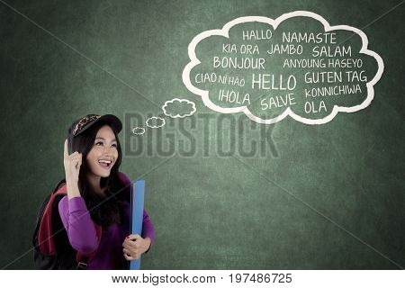 Image of pretty high school student learning multilingual while looking a cloud on the chalkboard