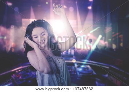 Image of a beautiful young DJ playing music while dancing in the night club