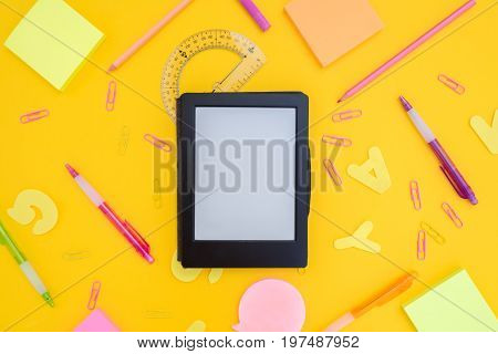 back to school or office styed scene with e-book and multicolored school supplies on yellow