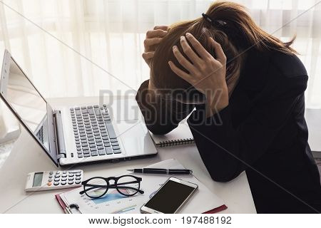 Stressed and frustrated asian business woman working with laptop in the office