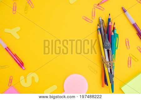 back to school or office styed frame with multicolored school supplies on yellow